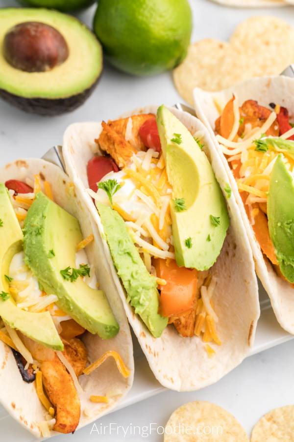 Chicken Fajitas ready to eat and topped with cheese, sour cream, and avocado slices.
