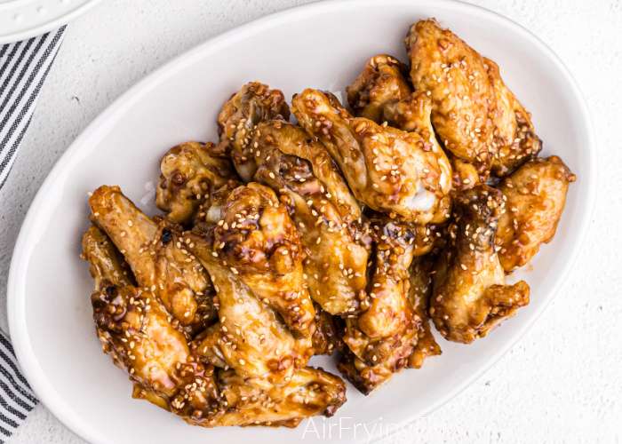 Honey Garlic Chicken Wings made in the Air Fryer - topped with sesame seeds and ready to serve on a white plate.