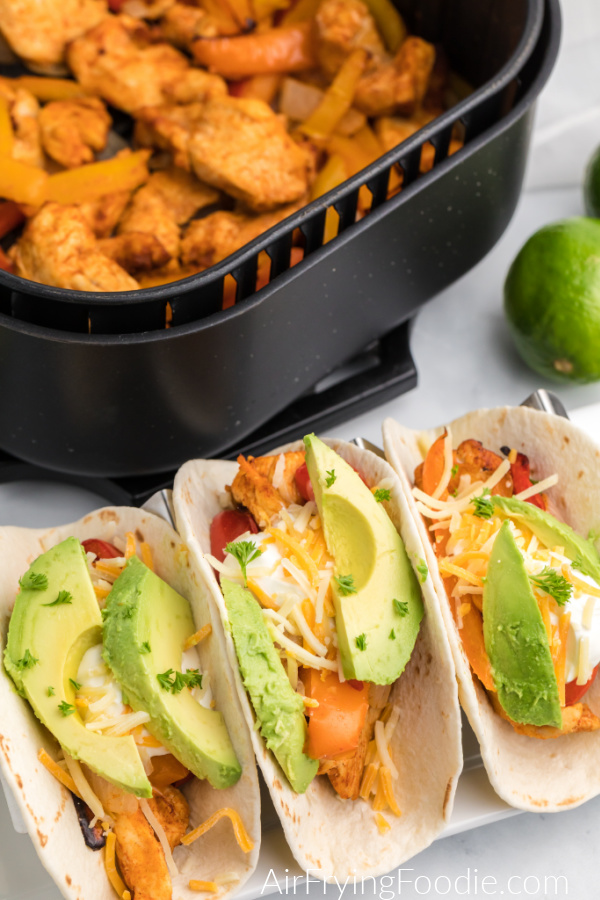 Fajitas on a plate and topped with cheese, sour cream, and avocado with chicken fajitas in the air fryer basket in the background.