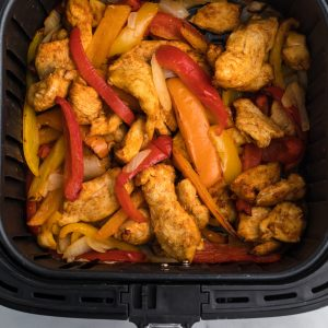 CHicken fajitas and vegetables in the air fryer basket.