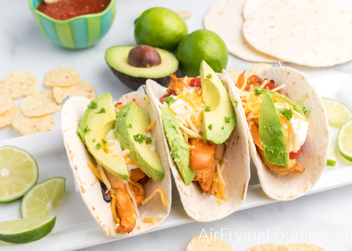 Chicken Fajitas made in the air fryer and topped with cheese, sour cream, and avocado on a plate with fresh limes.