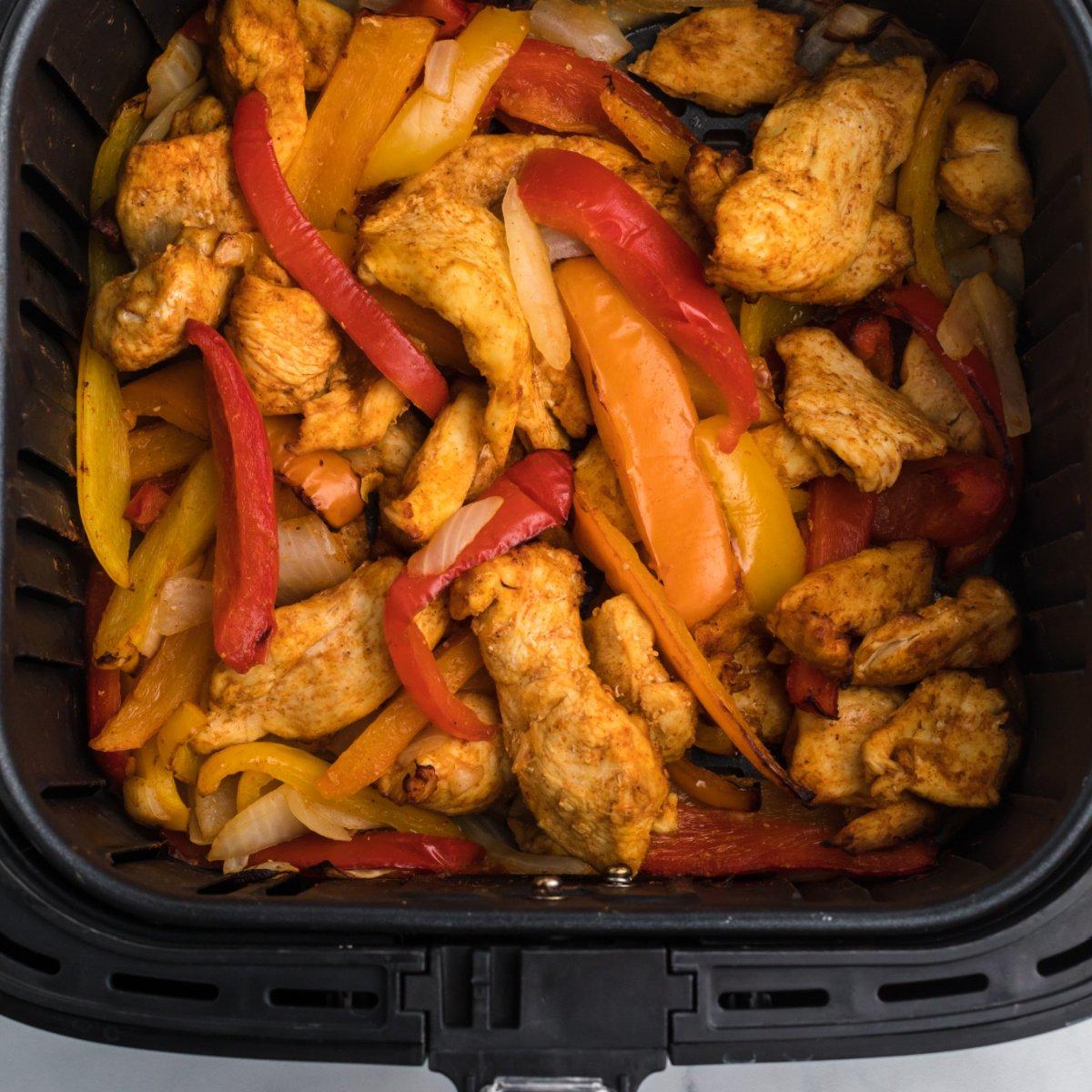 CHicken fajitas and vegetables in the air fryer basket.