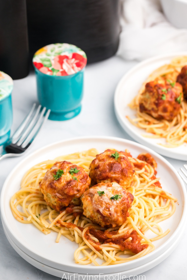 Air Fryer Chicken parmesan meatballs on a white plate with spaghetti noodles.