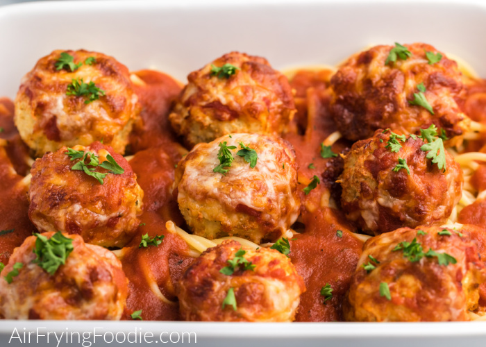 Chicken Parmesan meatballs on a bed of spaghetti in a white dish,