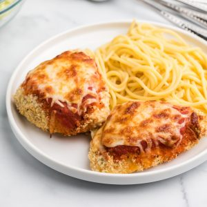 Air Fryer chicken parmesan on a white plate with spaghetti noodles.
