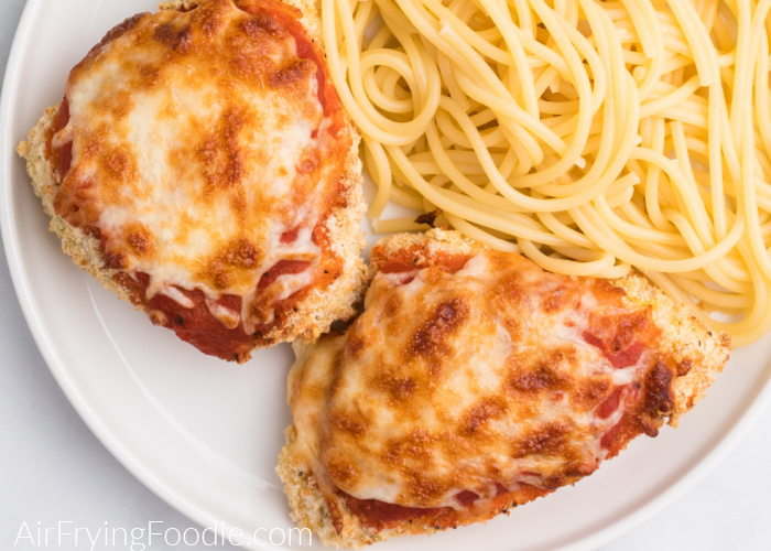 Chicken parmesan on a white plate with noodles.
