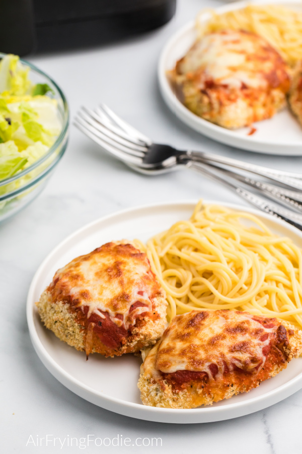 Chicken parmesan on white plate with spaghetti noodles and salad and an air fryer in the background.