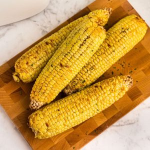 Golden ears of corn on a board, buttered and seasoned.