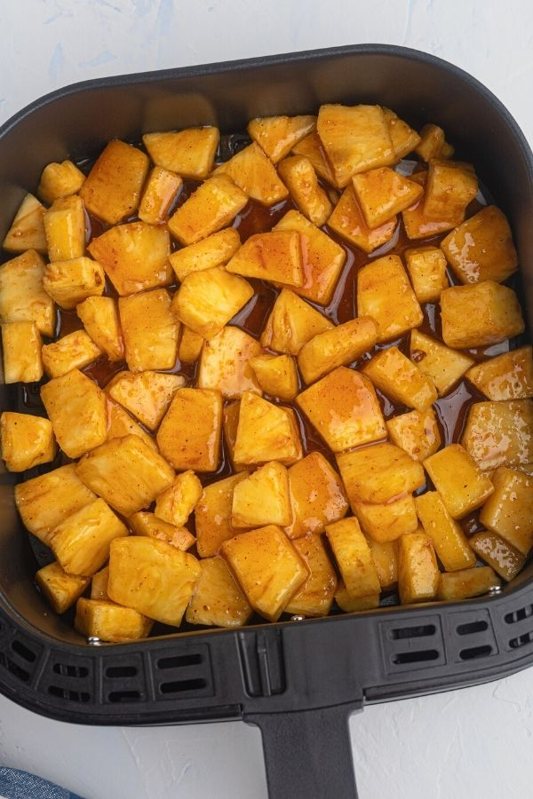 Uncooked pineapple pieces, covered in melted butter, sugars, and cinnamon, in an air fryer basket.