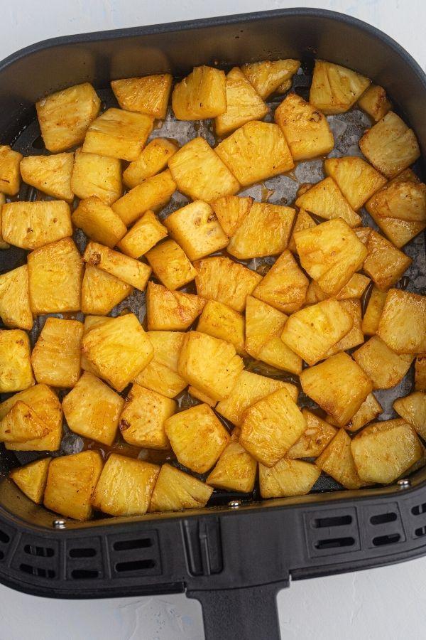 Cooked golden juicy pineapple in an air fryer basket.