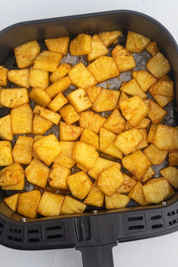 Juicy golden pineapple in the air fryer basket after being cooked in honey and bbq sauce.
