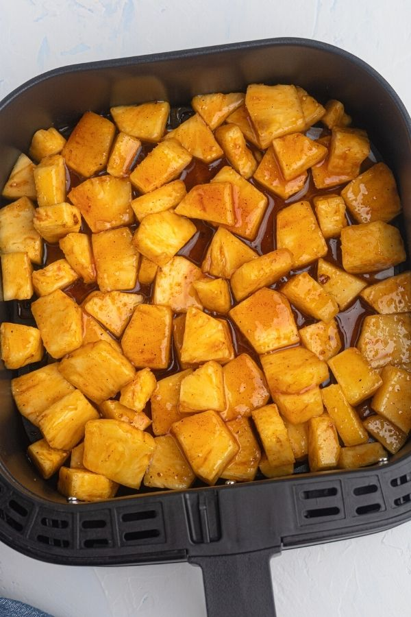 Juicy golden pineapple in the air fryer basket before being cooked in honey and bbq sauce.
