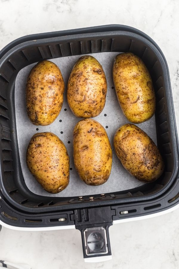 Potatoes in an air fryer basket on parchment paper before being cooked.