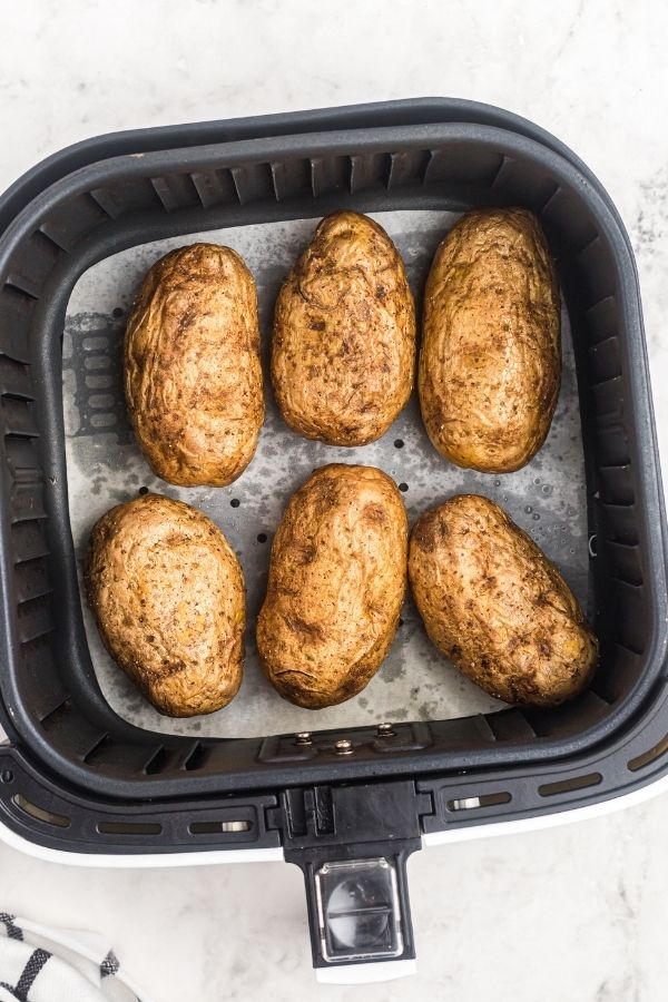 Cooked potatoes in the air fryer basked on white parchment paper.