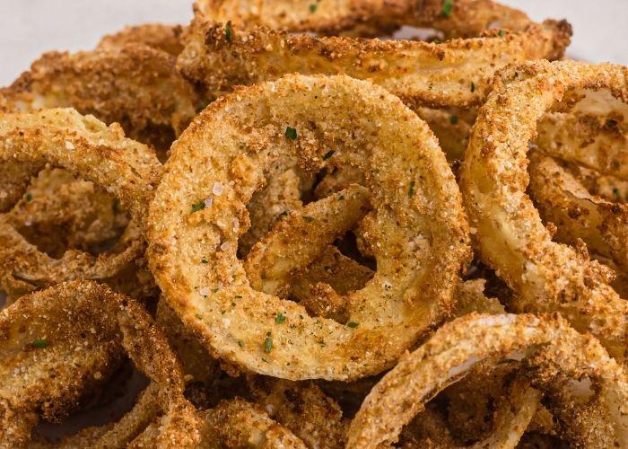 Close up photo of golden crispy onion rings.