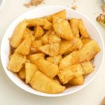 Golden juicy pineapple bites, in juices, served in a white bowl, topped with sprinkled brown sugar.