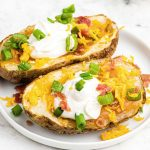 Potato skins topped with sour cream, cheese, bacon, and green onion, served on a white plate