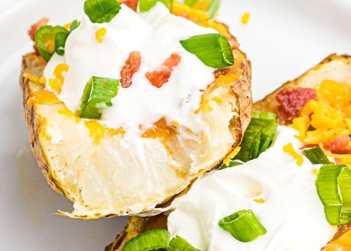 Close up photo of potato skin topped with melted cheese, bacon crumbles, sour cream, and chopped green onions, with a bite taken out of the potato skin.