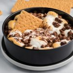 S'mores Dip in a springform pan with a graham cracker in the middle for serving.
