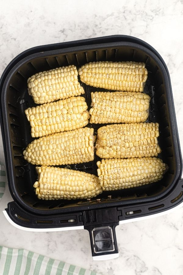 Uncooked corn on the cob, seasoned and buttered, in an air fryer basket.