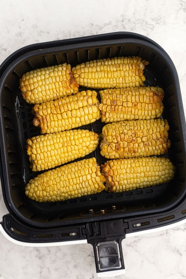 Cooked and golden, corn on the cob in an air fryer basket, seasoned with salt and pepper.
