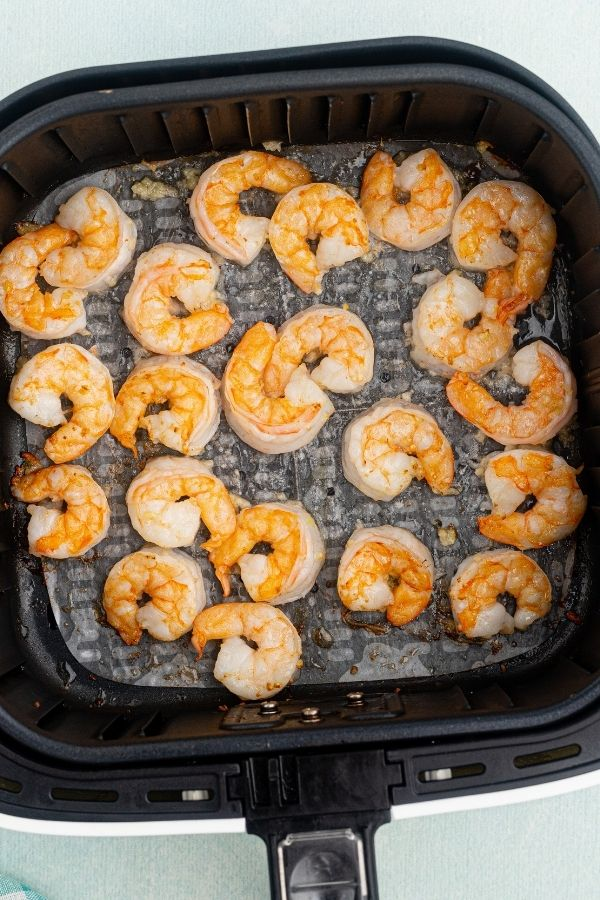 Cooked and orange golden color, shrimp tin the air fryer basket, coated with butter and garlic.