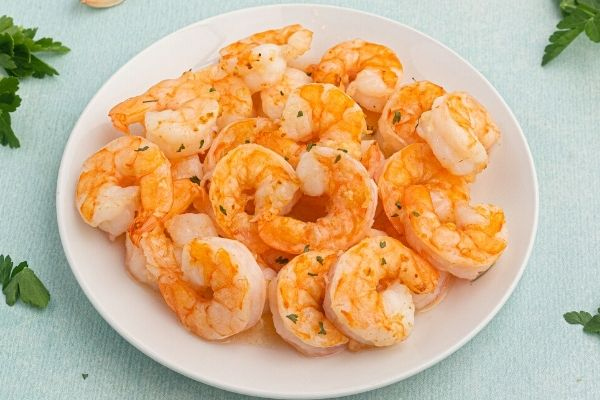 Golden air fryer shrimp, cooked and served on a white plate.