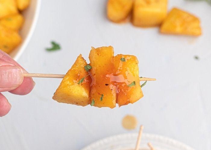 Juicy glazed pineapple on a toothpick.