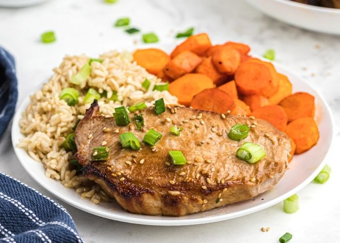 Juicy pork chop served on a white plate with rice and carrots. Topped with sesame seeds and chopped green onions.
