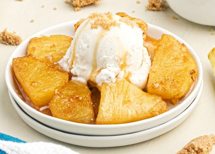 Juicy golden pineapple in juices, topped with vanilla ice cream and caramel sauce, served on a white plate.
