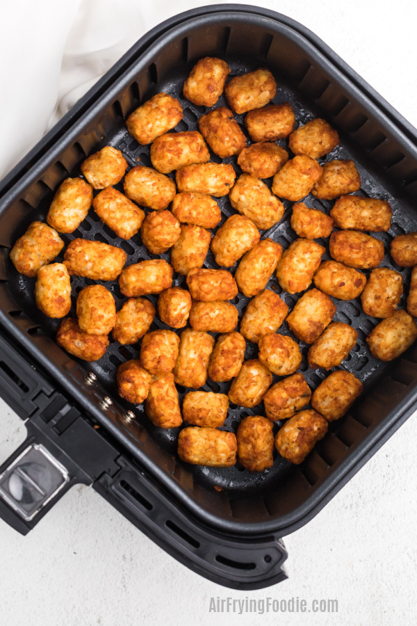 Tater Tots fully cooked in the basket of the air fryer.