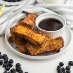 French toast sticks made in the air fryer on a white plate with blueberries surrounding it.