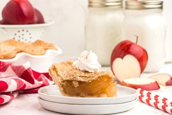 Golden crust, apple pie, served on white plates, with glasses of milk and cut up apples in the background.