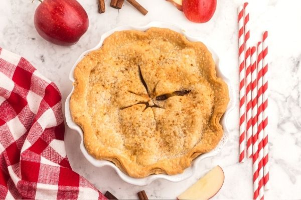 Apple pie with a golden crust, on a white marble table with sliced red apples and cinnamon sprinkled on top.