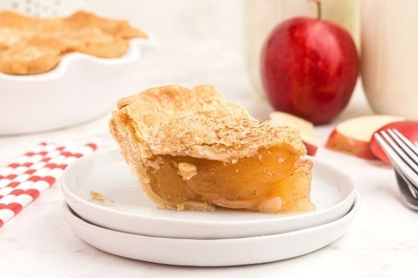 Slice of apple pie on a whit plate with red apple, milk, and forks on the table.