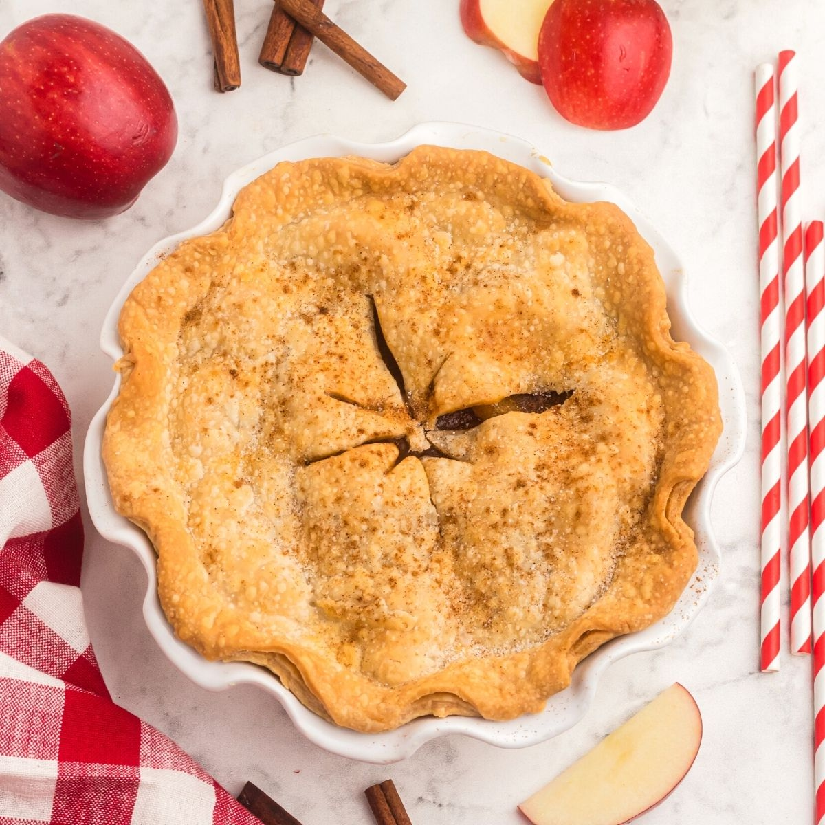 Golden baked apple pie, with red apples and red and white straws on the table.