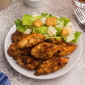 Blackened chicken served on a white plate with a salad.