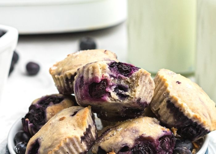 Mini muffins stacked with a bite taken. Milk and fresh blueberries on the table.