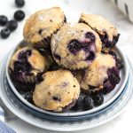 Blueberry muffins stacked on a white plate with fresh blueberries scattered around the table.