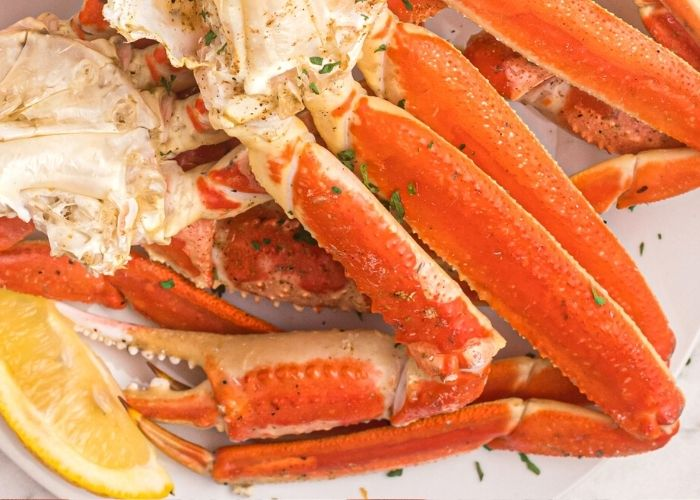 Juicy crab legs, orange in color, with lemon slices served on a white plate with parsley flakes.