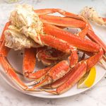 Orange crab legs on a white plate, served with lemon slices and sprinkled with parsley flakes.
