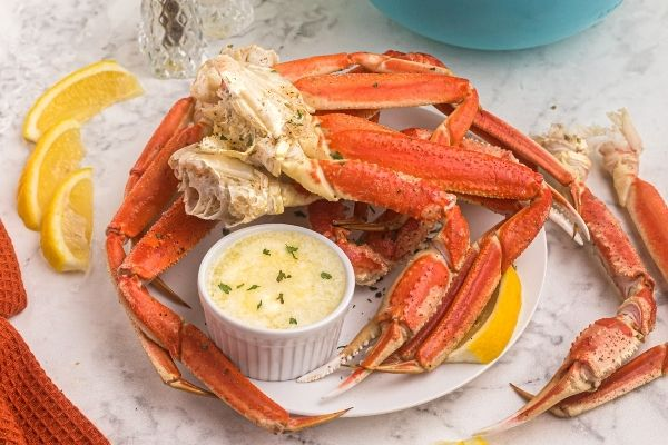 Moist and orange crab legs, on a white plate, served with lemon slices and melted butter on a marble table.