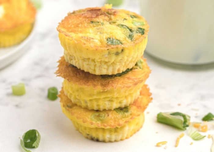 Egg bites stacked in a row of three, with chopped green onions scattered on the table.