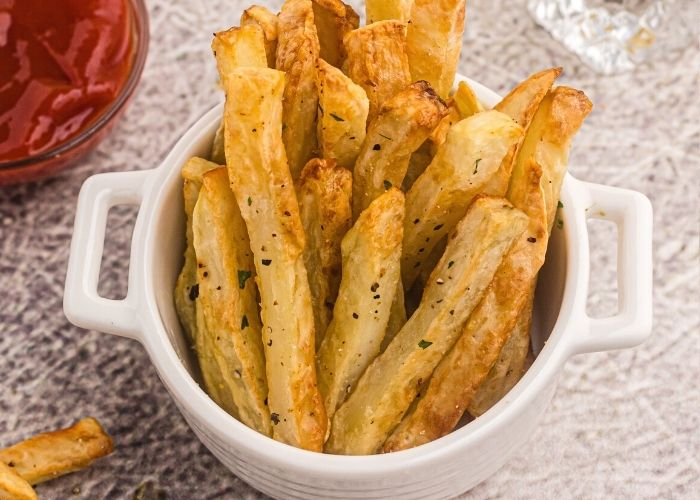 Crispy golden french fries in a small white bowl, seasoned with salt and pepper and parsley flakes.