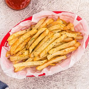 golden crispy french fries in a red basket, served with ketchup.