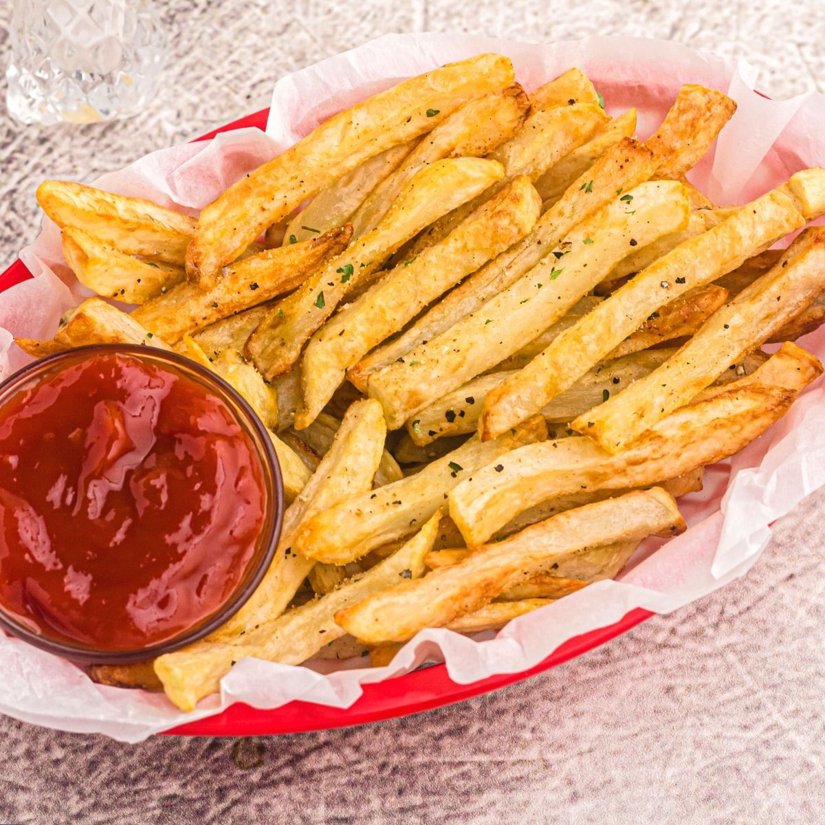 Golden and crispy, seasoned french fries served in a red basket with ketchup.