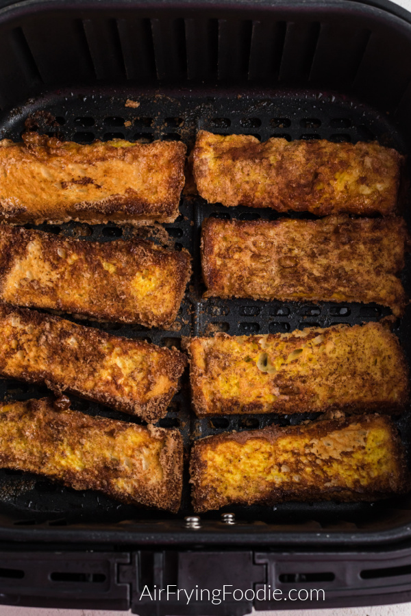 French toast sticks lined in the air fryer basket after being cooked - ready to remove from the basket for serving.
