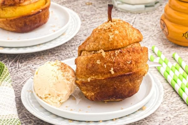 Golden pear wrapped in a layer of puff pastry strips. Served on a white plate with vanilla ice cream.
