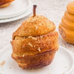 Golden pear wrapped in a puff pastry, sprinkled with brown sugar and served on a white plate.
