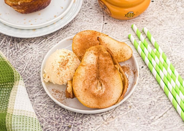 Cooked golden pear, served with vanilla ice cream, and sprinkled with cinnamon, served on a white plate.